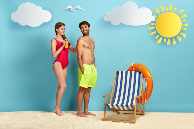 A esposa carinhosa aplica protetor solar nas costas do marido para proteção da pele durante o banho de sol