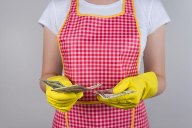 A esposa encontrou economias extras com o conceito de marido. cortado perto de uma senhora alegre e feliz segurando uma pilha de dinheiro nas mãos, verificando a quantia vestindo roupas vermelhas, parede cinza isolada