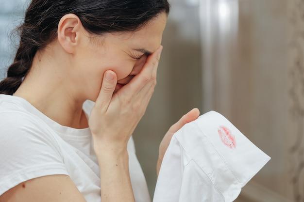 A esposa encontrou vestígios do batom de outra pessoa na camisa do marido. homem trapaceando