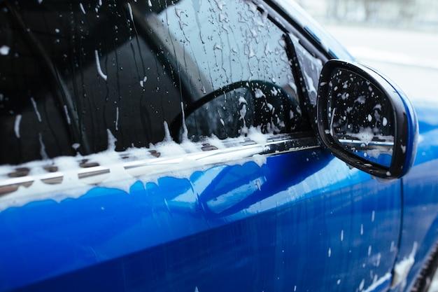 A espuma de sabão escorre pelo vidro. lavagem de carros self-service