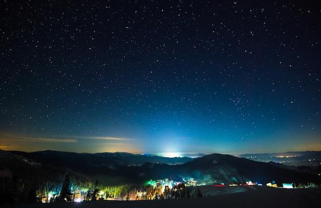 A estação de esqui iluminada à noite está localizada em um lugar pitoresco acima de um céu estrelado.