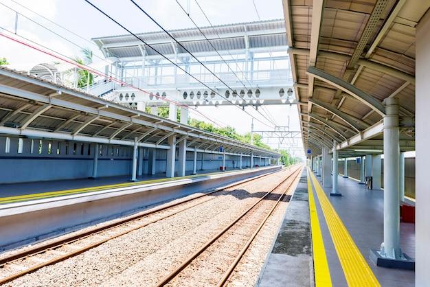 A estação de trem com uma ponte de pedestres acima dela