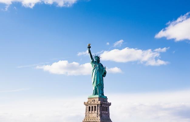 A estátua da liberdade com céu bonito nublado