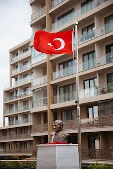 A estátua de ataturk e bandeiras turcas em frente ao edifício em tempo nublado. conceito de símbolos turcos.