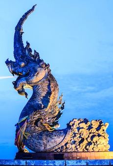 A estátua de phaya naga borrifou água e o céu noturno.