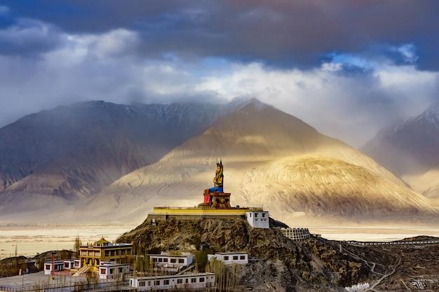 A estátua do buda maitreya com montanhas do himalaia ao fundo do mosteiro de diskit