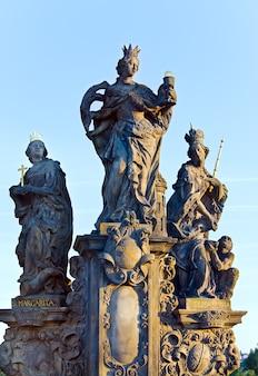 A estátua dos santos bárbara, margarida e elizabeth na noite da ponte carlos (praga, república tcheca). esculpido por ferdinand brokoff em 1707