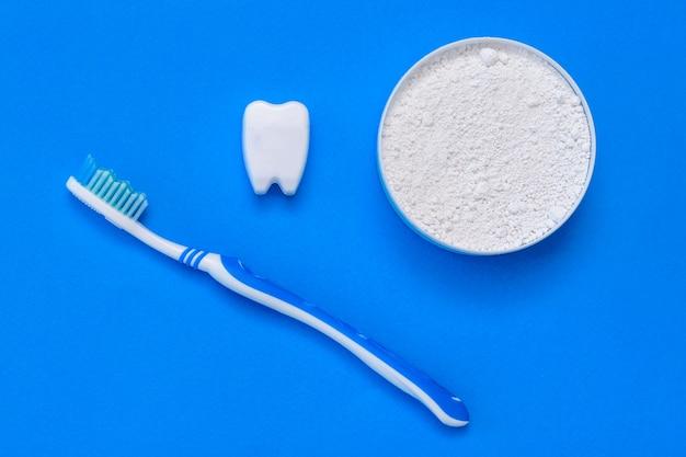 A estatueta de dente sorri ao lado do pó e da escova de dentes. postura plana.