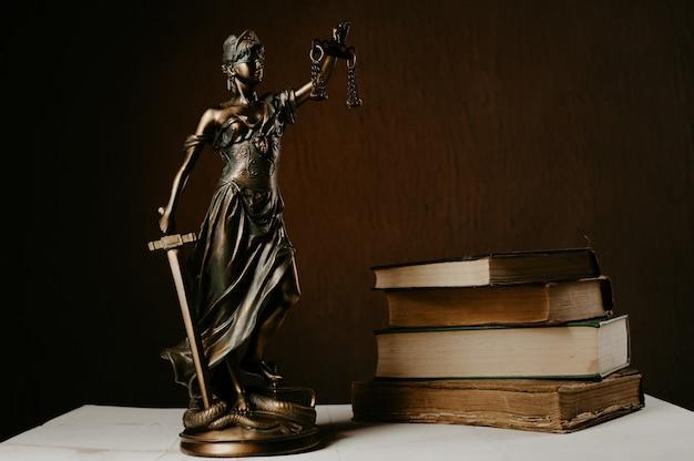 A estatueta de themis fica em uma mesa de madeira branca ao lado de uma pilha de livros antigos.