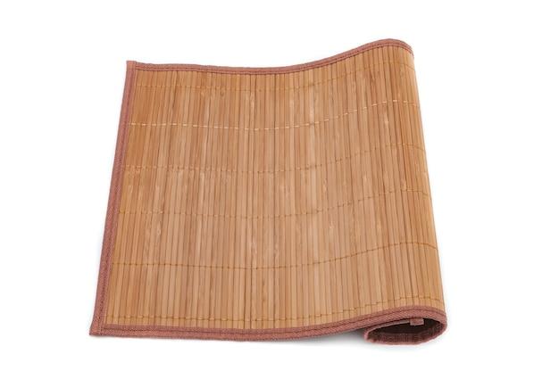 A esteira de bambu em um fundo branco está dobrada de um lado.