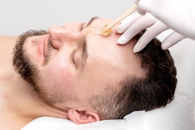 A esteticista aplica cera entre as sobrancelhas masculinas antes do procedimento de depilação no salão de beleza.