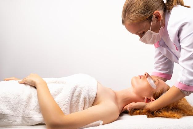 A esteticista dá à mulher uma foto profissional de massagem de rosto e pescoço em uma parede branca
