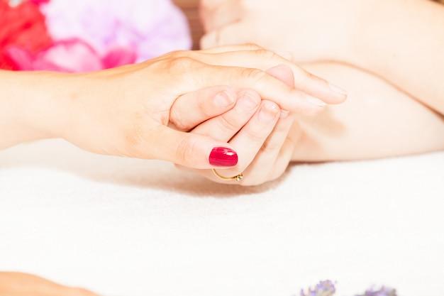 A esteticista decora com flores as unhas das mãos do cliente