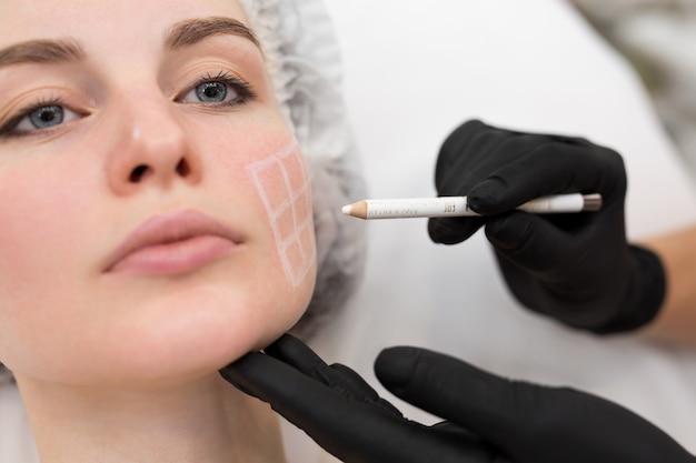 A esteticista desenha os contornos de um lápis branco no rosto da paciente.