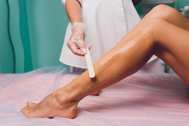 A esteticista está se preparando para a depilação e aplicando o creme com um bastão de cera nas belas pernas femininas. salão de beleza.