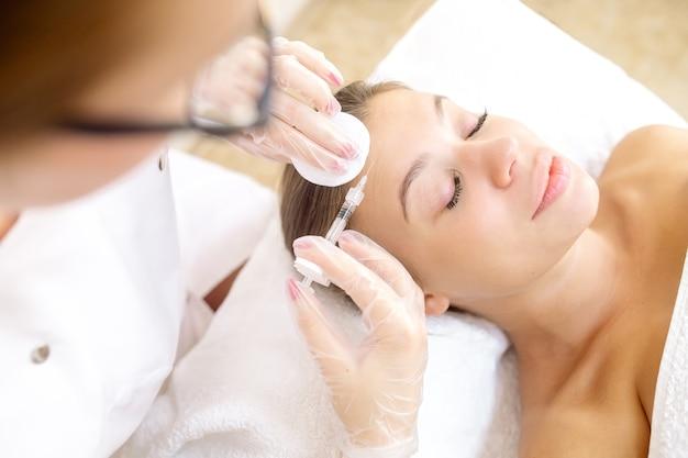A esteticista faz correção de rugas na paciente com botox na testa e entre as sobrancelhas
