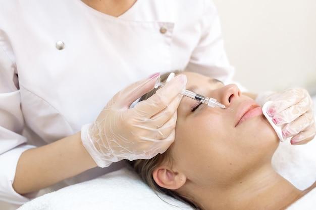 A esteticista faz o aumento dos lábios do paciente