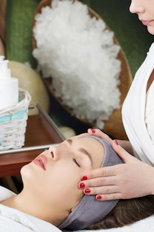 A esteticista faz uma massagem de rosto para uma jovem em um salão de spa