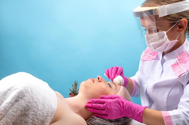 A esteticista faz uma massagem facial em uma jovem usando um balcão redondo de massagem. spa e beleza na pandemia: máscara, tela e luvas.