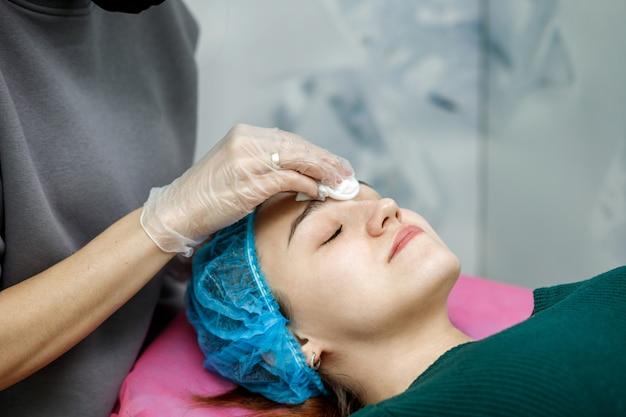 A esteticista limpa o rosto com um guardanapo após os procedimentos para a jovem deitada em um sofá