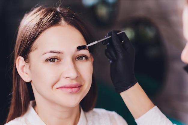 A esteticista- maquiadora aplica hena de tinta nas sobrancelhas aparadas, desenhadas anteriormente, em um salão de beleza na correção da sessão. cuidado profissional para o rosto.