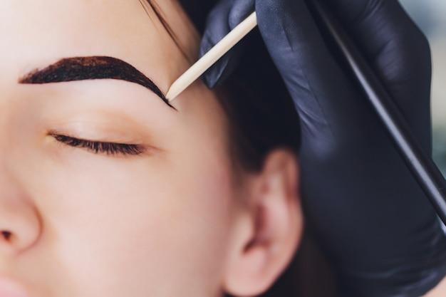 A esteticista- maquiadora aplica hena de tinta nas sobrancelhas aparadas, desenhadas e previamente arrancadas em um salão de beleza na correção da sessão. cuidado profissional para o rosto.