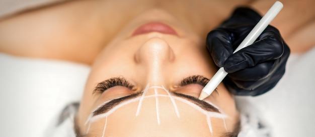 A esteticista marca a sobrancelha com um lápis branco para preparar um procedimento de maquiagem definitiva