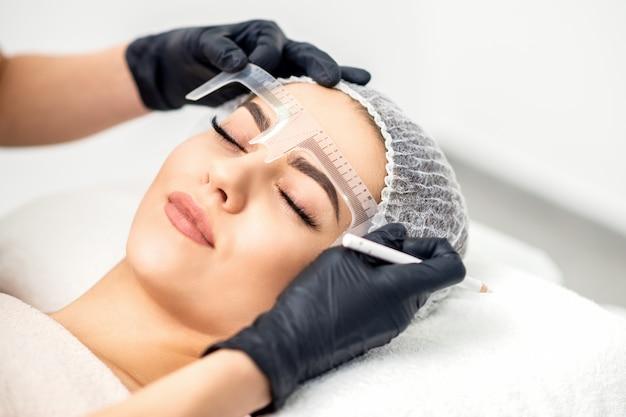 A esteticista mede as sobrancelhas com uma régua antes de tatuá-las