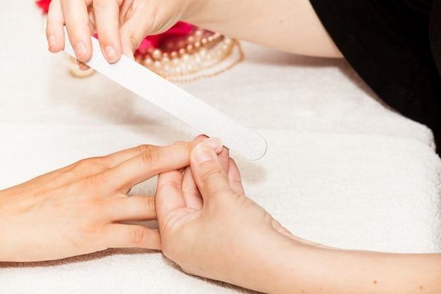 A esteticista polonês unhas do cliente antes de colocar unha polonês