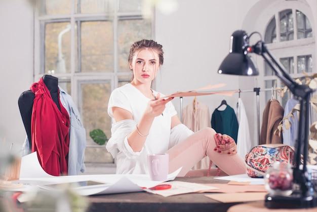 A estilista feminina trabalhando em um estúdio, sentada na mesa