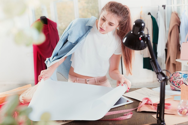 A estilista feminina trabalhando sentada na mesa
