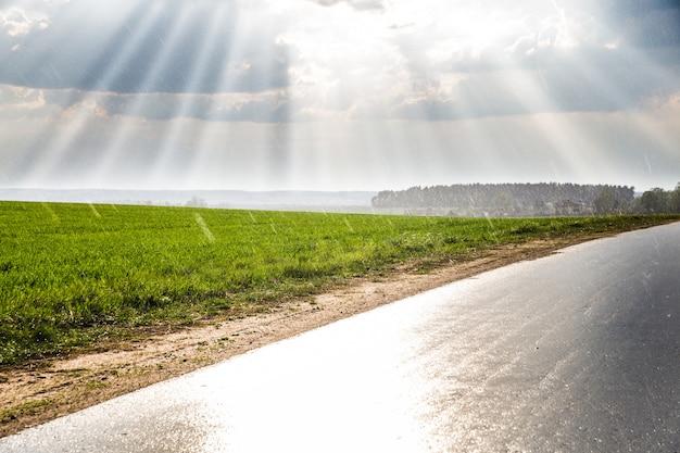 A estrada ao longo do campo verde