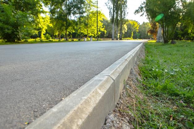 A estrada caminho no parque da cidade com árvores e grama