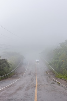A estrada na montanha é coberta por nevoeiro