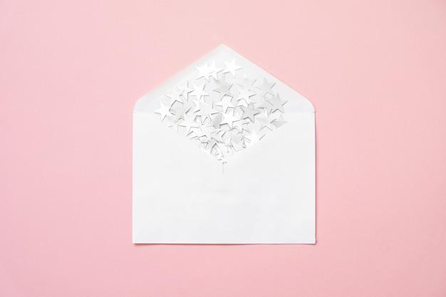 A estrela de prata polvilha confetes no envelope no fundo cor-de-rosa. natal mínimo.