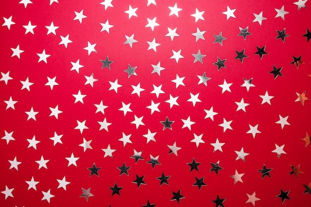 A estrela de prata polvilha no backgound vermelho. confete de férias festivas. conceito de celebração.