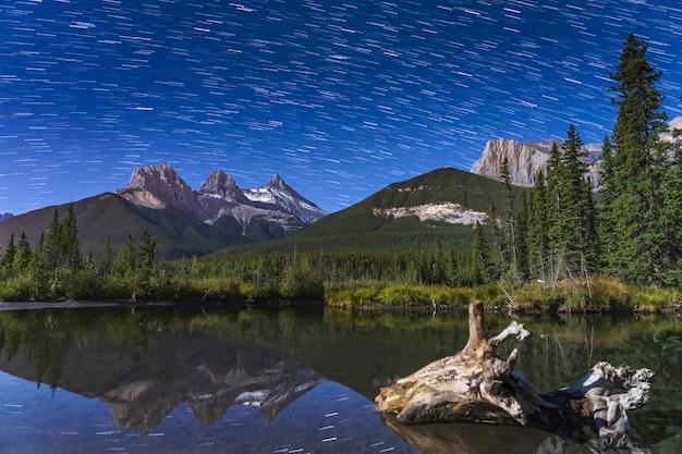 A estrela trilha acima do trio das três irmãs no pico da montanha à noite. canmore, canadian rockies, alberta, canadá.