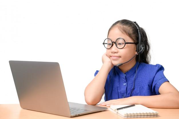 A estudante asiática veste o estudo sem fio do auscultadores em linha em casa.