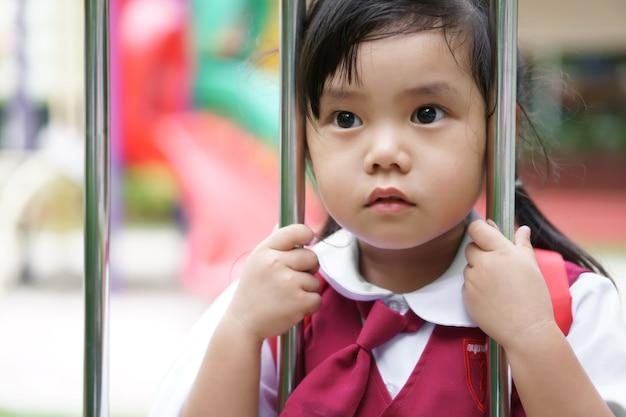 A estudante asiática veste uniforme escolar e vai para a escola e mantém cerca de aço inoxidável