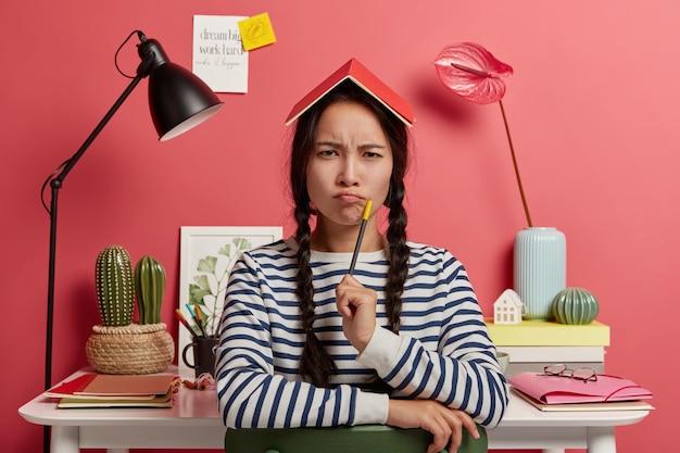 A estudante coreana inteligente tem um olhar sério e taciturno, franze os lábios, segura o lápis e o bloco de notas na cabeça