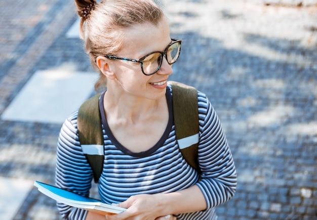 A estudante de sorriso bonito da menina com os livros nos vidros está perto da faculdade.