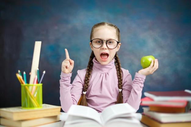 A estudante elementar consideravelmente caucasiana faz trabalhos de casa