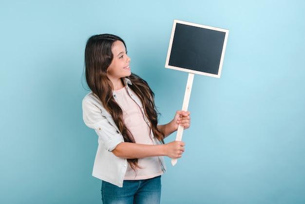 A estudante está guardando uma placa vazia em suas mãos e olhando nela.