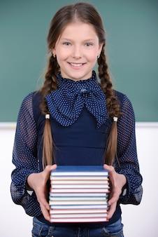 A estudante está prendendo livros em suas mãos e sorrindo.