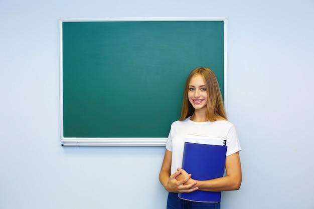 A estudante feliz perto do quadro-negro, do quadro-negro e guarda a pasta
