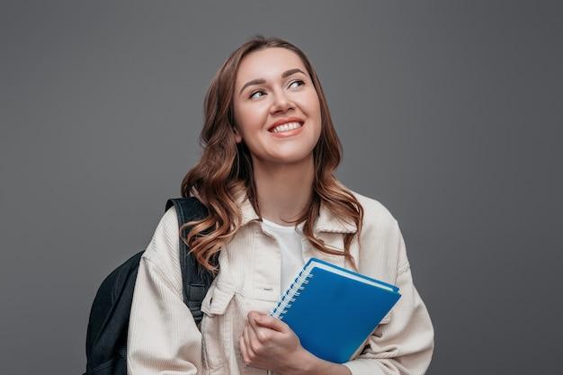 A estudante feliz ri e sorri e olhando afastado mantendo um caderno isolado sobre a parede cinzenta escura. conceito de vestibular