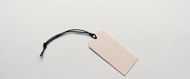 A etiqueta de preço de papelão está vazia, sem inscrições sobre um fundo claro. a luz cai de um lado, há uma sombra.