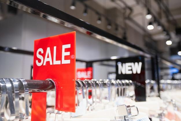 A etiqueta vermelha da venda na roupa submete na loja da roupa da mulher.