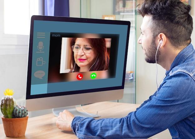 A exibição na tela de laptops com 50 mulheres maduras do grupo líder de chamadas de vídeo distantes conversa com diferentes grupos étnicos de mulheres da idade. vista por cima do ombro da menina sentada no