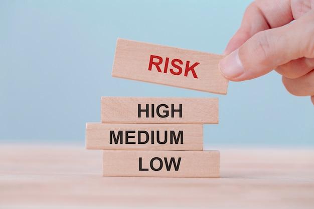 A exploração da mão escolhe cubos de madeira do bloco com palavra do risco. conceito de gerenciamento de riscos.